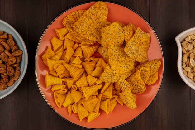 Top view of spicy crispy chips on an orange dish with pine nuts on a bowl on a wooden table
