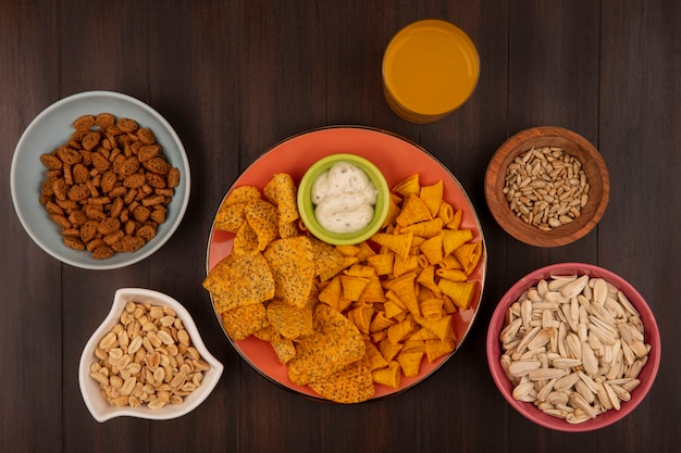 Top view of spicy crispy chips on an orange dish with sauce on a bowl with shelled sunflower seeds on a wooden bowl with pine nuts on a bowl with a glass of orange juice on a wooden table
