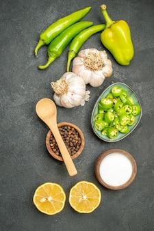 Peperoni verdi piccanti vista dall'alto con limone e aglio su uno sfondo scuro