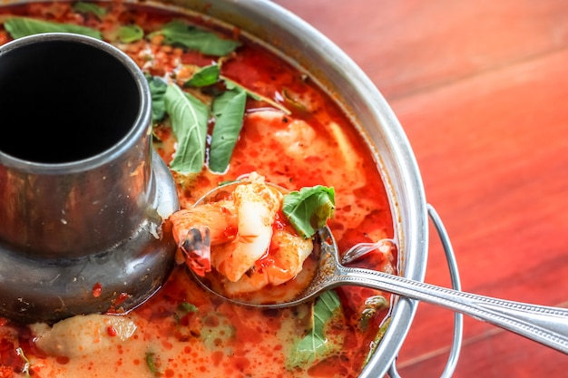 Top view spicy tom yum goong thai style in the hot pot, spicy soup, a classic spicy lemongrass and shrimp soup recipe from thailand