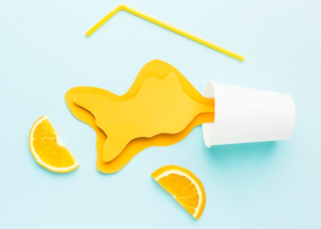 Top view of spilled paper juice with straw and orange slices