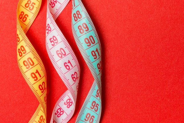Top view of spiral colorful measure tapes on red background.