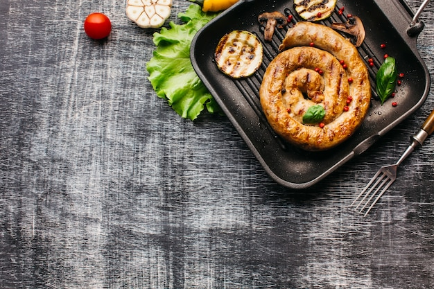 Top view of spiral grilled sausage with vegetable in pan