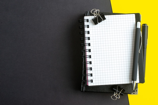 Top view of spiral notebook on book and pens on black yellow background with free space
