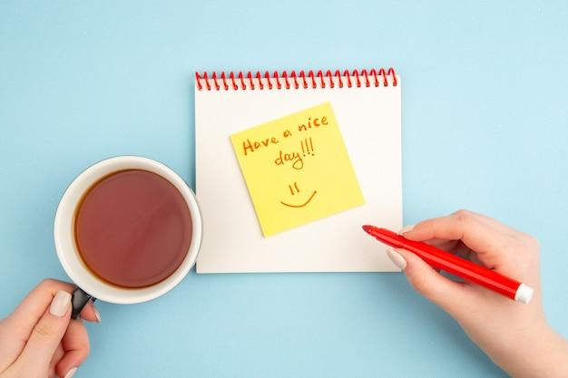 Вид сверху спиральный блокнот с чашкой чая и красным маркером в женских руках хорошего дня, написанного на липкой записке на синем
