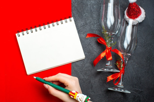 Top view of spiral notebook and hand holding a pen next to glass goblets santa claus hat on red and black background