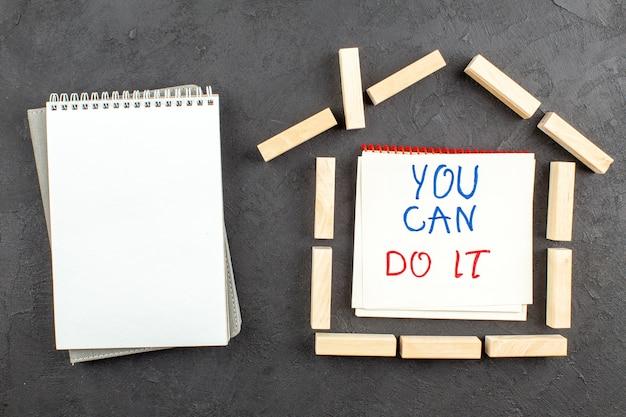 上面図スパイラルノートの家の形をした木製のブロックあなたはそれを黒のノートに書くことができます