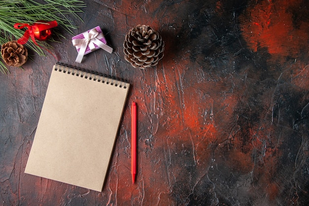 Top view of spiral notebook pen conifer cone gift and gift on dark background