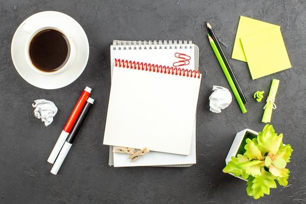 上面図スパイラルノート赤と黒のマーカー緑と黒の鉛筆黒にお茶の付箋のカップ
