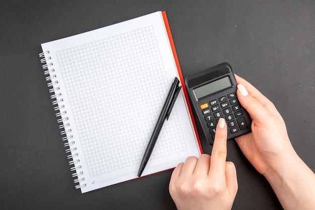 Вид сверху спиральный калькулятор блокнота в женской ручке на темноте