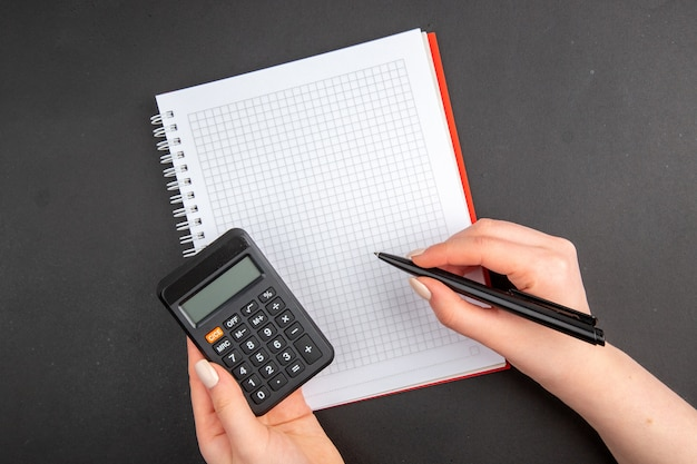 Top view spiral notepad calculator and pen in female hands on dark
