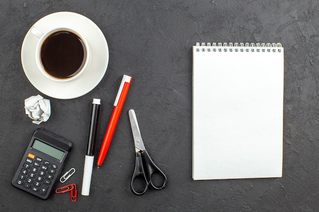 Top view spiral notepad scissors calculator cup of tea red pen and black marker on black