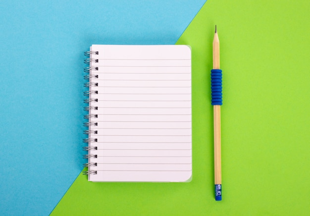 Top view of spiral notepad and wooden pencil on blue-green background. flat lay style.