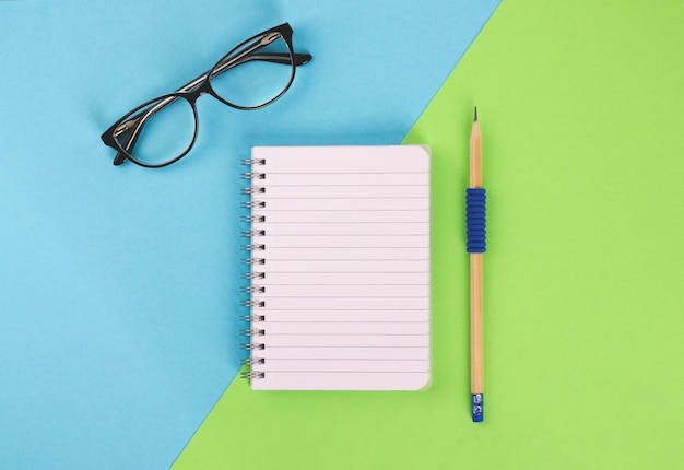 Top view of spiral notepad, wooden pencil and glasses on blue-green background.