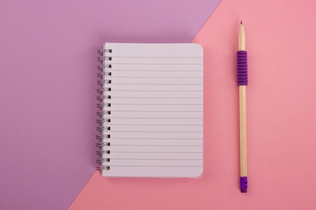 Top view of spiral notepad and wooden pencil on pink-lavender background. flat lay style.