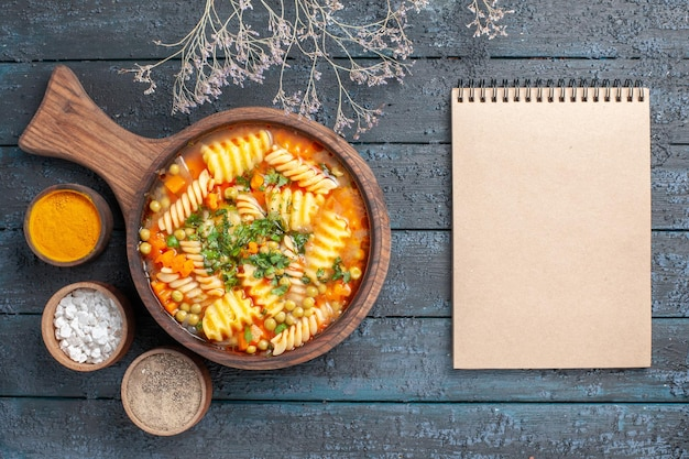 Vista dall'alto zuppa di pasta a spirale pasto delizioso con diversi condimenti sulla cucina di piatto di pasta italiana colore zuppa da scrivania blu scuro