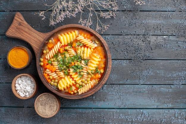 Vista dall'alto zuppa di pasta a spirale pasto delizioso con diversi condimenti sulla cucina di piatto di pasta italiana color zuppa scura da scrivania