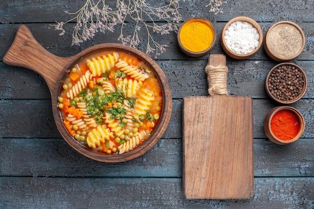 トップビュースパイラルパスタスープダークデスクで調味料を変えた美味しいお食事スープカラーイタリアンパスタ料理