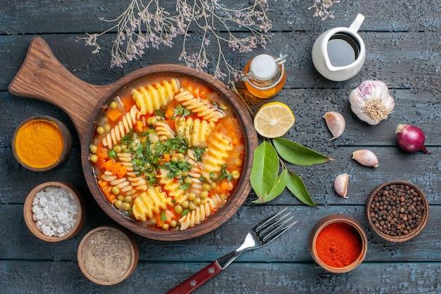 Zuppa di pasta a spirale vista dall'alto con condimenti sul piatto di cucina di pasta italiana colore salsa di zuppa da scrivania blu scuro