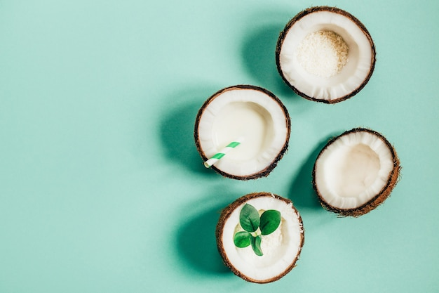 Top view of split coconut on green background