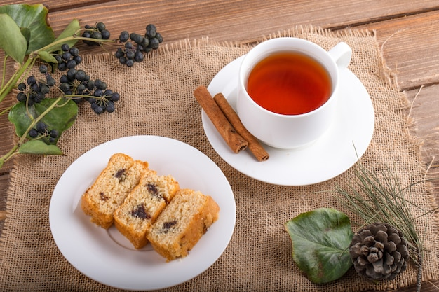 Top view of sponge cake slices on a plate with a cup of black tea on rustic background
