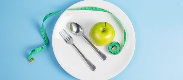 상위 뷰 스푼과 포크, 파란색 배경에 녹색 측정 테이프가 있는 흰색 세라믹 접시에 녹색 사과. 다이어트, 체중 감량, 비만 및 식품 조절 개념