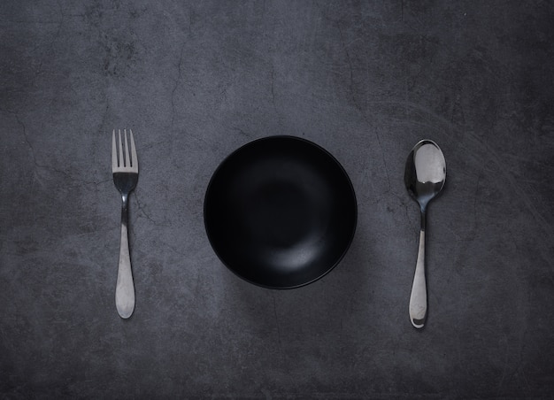 Top view of spoon and empty bowl on dark cement table