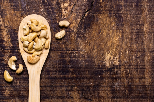 Top view of spoon with cashews and copy space