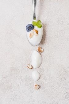 Вид сверху ложка с органическим йогуртом на столе