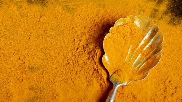 Top view of spoon with turmeric with copy space