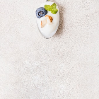 Top view spoon with yogurt and fruits