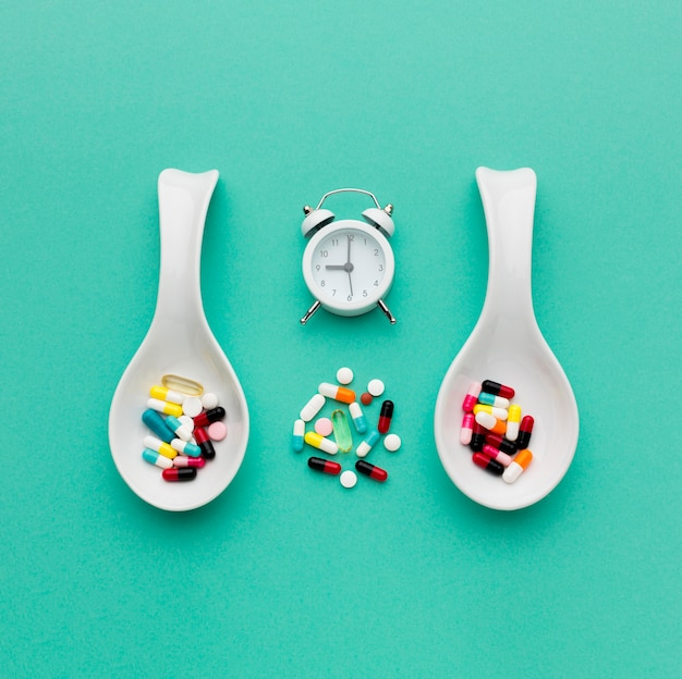Top view spoons with pills and clock