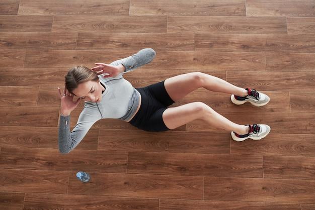 Вид сверху. спортивная молодая женщина имеет фитнес-день в тренажерном зале в утреннее время