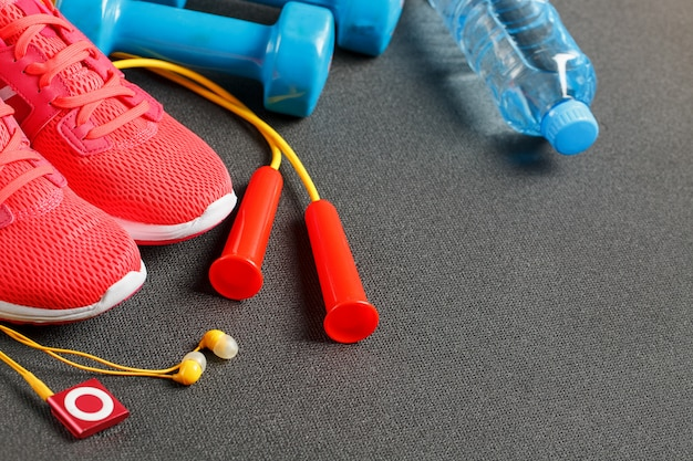 Top view of sports equipment, dumbbells, a skipping rope, a bottle of water, sneakers and a player. isolated on a gray