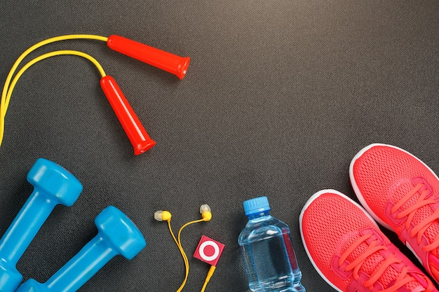 Top view of sports equipment, dumbbells, a skipping rope, a bottle of water, sneakers and a player