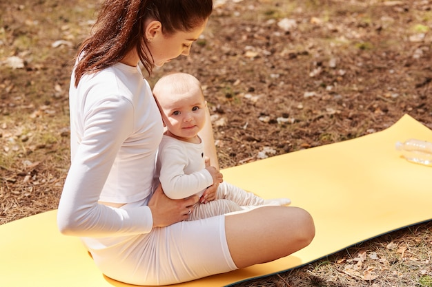 Top view of sporty woman with infant kid sitting on karemat in lotus pose, keeping legs crossed