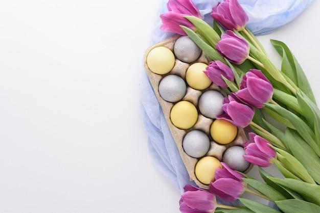 上面図白い背景の上の卵と紫色のチューリップの春のお祭りイースター構成