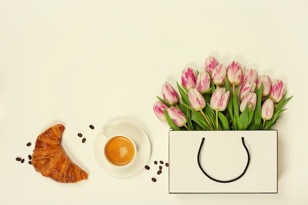 Top view of spring flowers, coffee and croissant