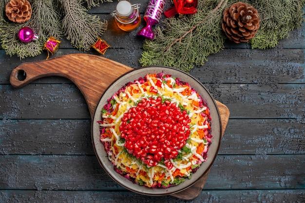 Piatto di rami di abete rosso vista dall'alto con semi di melograno sul tagliere accanto ai rami di abete con coni e giocattoli per alberi