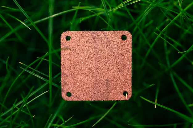 Top view of square brown leather patch for clothing creative layout of lawn green grass with logo tag.