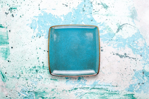 Top view square plate blue colored empty on light blue surface plate glass color food