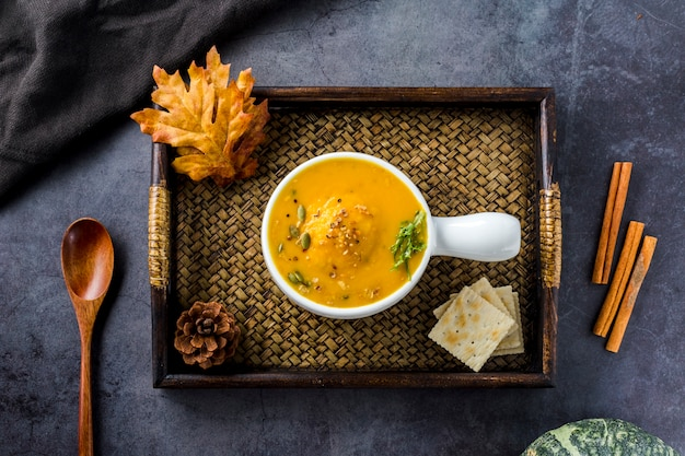 Top view of squash soup on wooden tray
