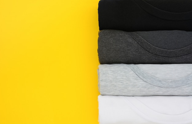 Top view stack of black, grey and white t-shirt rolled up on yellow