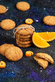 Top view of stack of homemade cookies with orange slice over dark table.