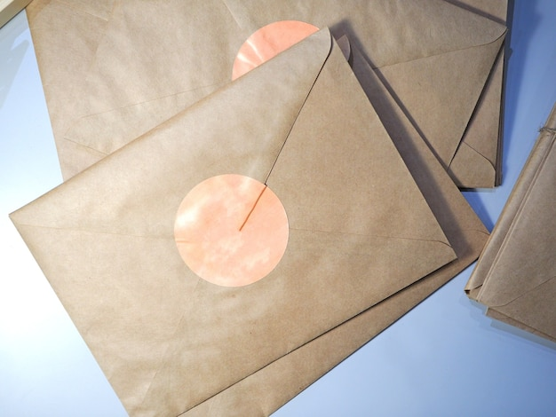 Top view of a stack of letters in kraft envelopes lying on the table tied with string
