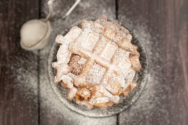 Top view of stacked waffles with powdered sugar on top