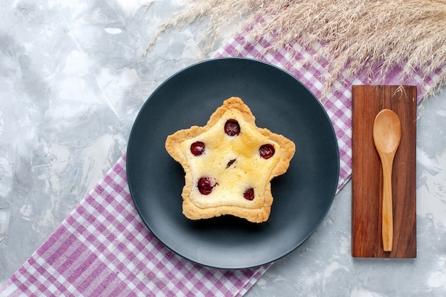 Top view star shaped cake with cherries inside on the light table cake sweet sugar tea bake pie