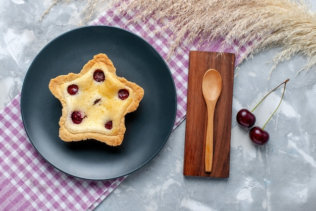 Top view star shaped cake with cherries inside plate on the light table fruit bake cake biscuit sweet