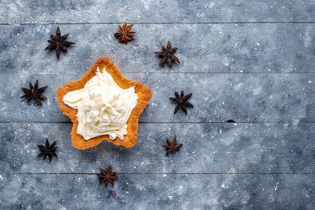 Torta a forma di stella vista dall'alto con crema sullo sfondo chiaro torta biscotto zucchero dolce cuocere la crema