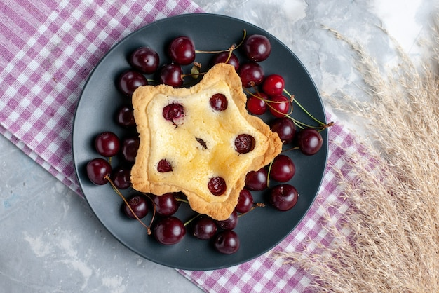 Top view star shaped cake with fresh sour cherries inside plateo n the light table fruit cake bake pie color cherry